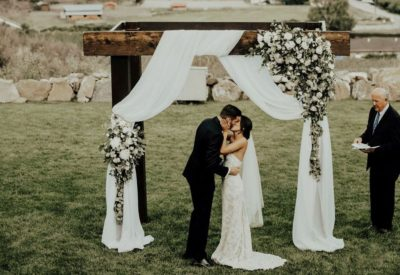 Couple kiss under a bridal arche at a wedding)