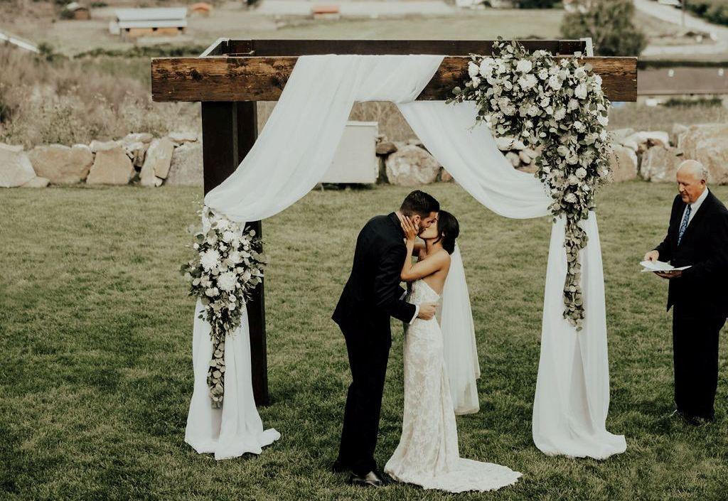 Couple kiss under a bridal arche at a wedding)