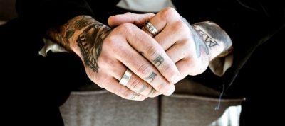 Tattooed man wear diamond rings on his hands in a tuxedo