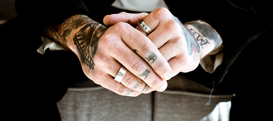 Tattooed man wear diamond rings on his hands in a tuxedo