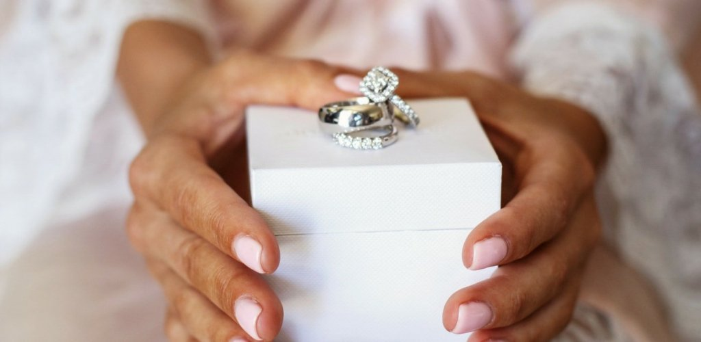 Woman holds a box with a stack of diamonds rings on top
